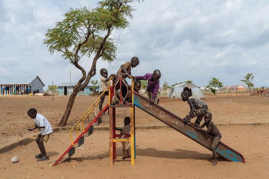 Children climb on a slide in a playground at a Northern Ugandan refugee camp.