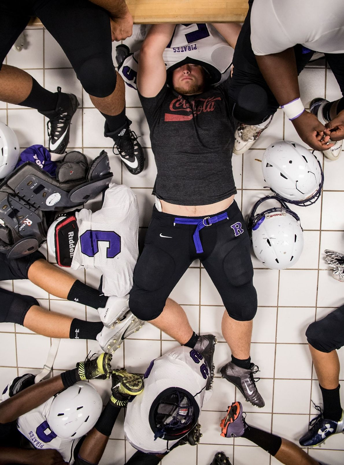 """""""Thomas Weaver rests with his Riverside high school teammates during a rain delay of an away ..."""