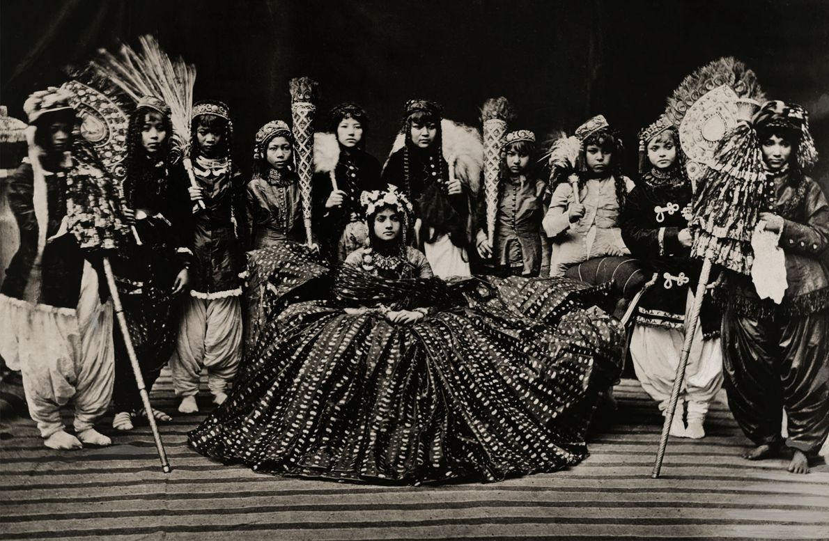 Ladies in waiting fan out around the Queen of Nepal, probably taken in the 1910s.