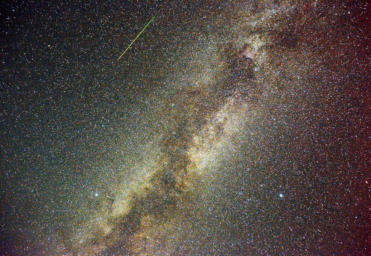 In this multiple exposure image, a Perseid meteor leaves a green streak in the skies over ...