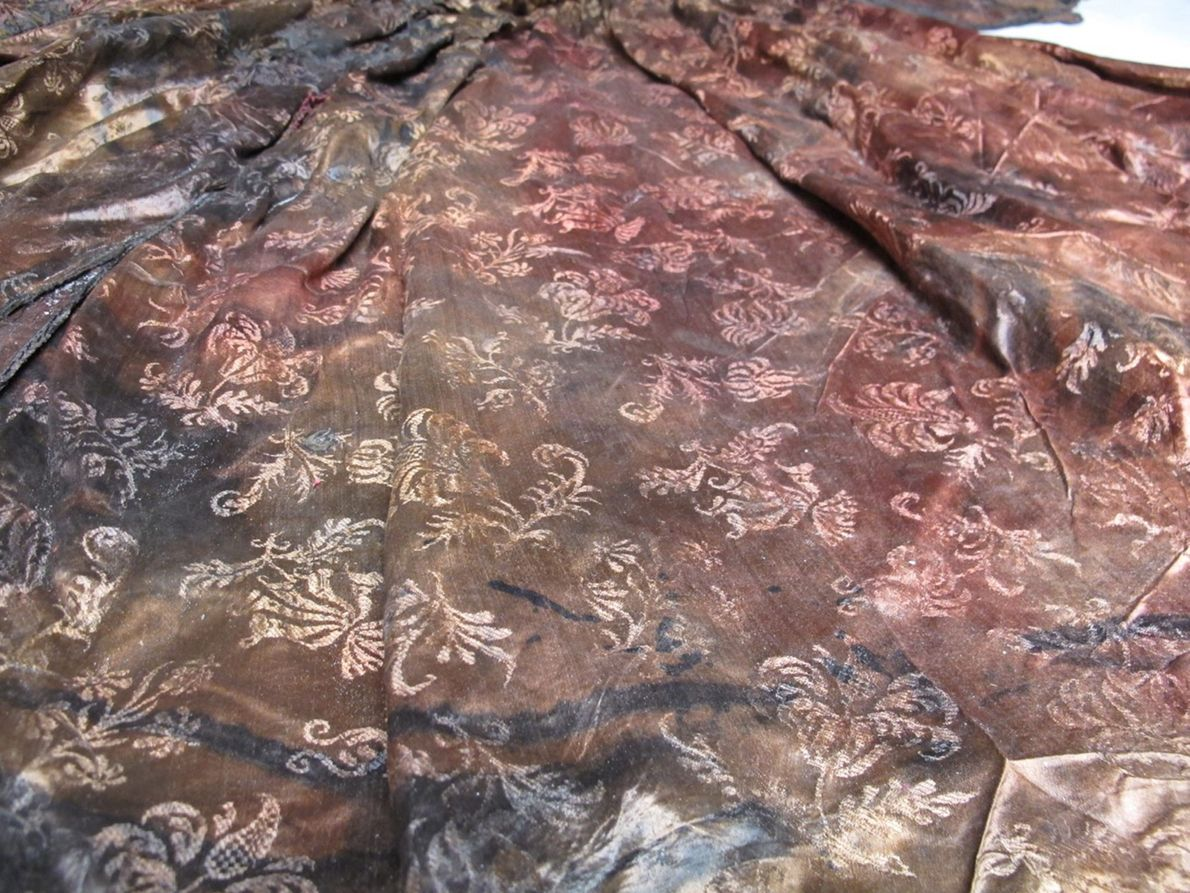 This detail from the gown shows its elaborate floral damask embroidery. While the fabric is now ...