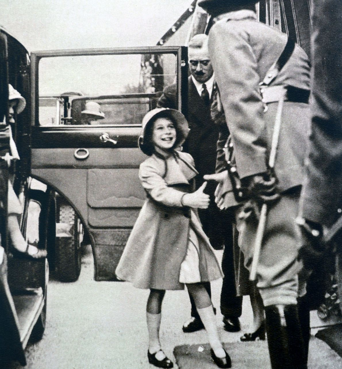 Queen Elizabeth II, then eight years old, greets an officer of the guard outside the Rushmoor ...