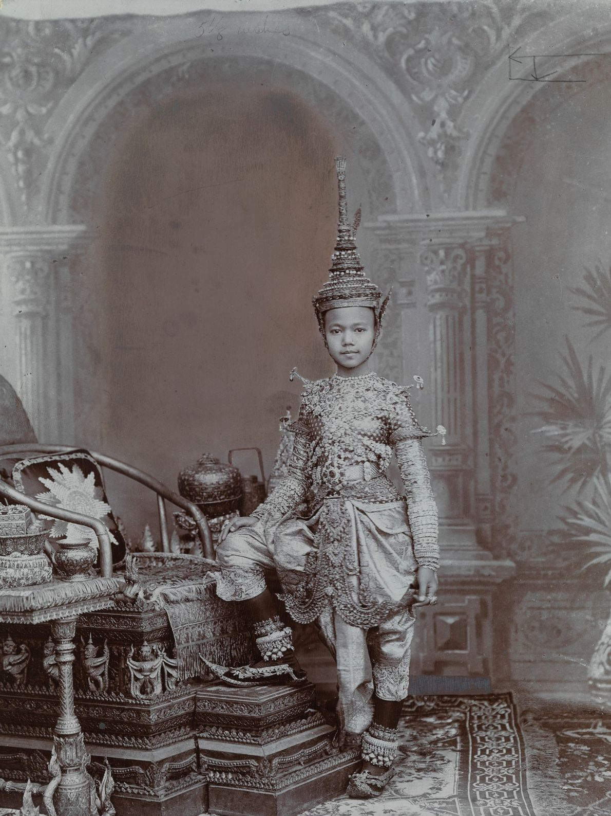 A Siamese prince wears a full regalia of jewels, including a headpiece modeled after a 'chadok', ...
