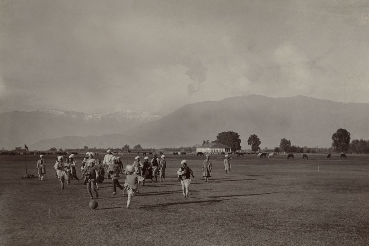 In a vast field at the foot of the Himalaya, children play a pickup game of ...