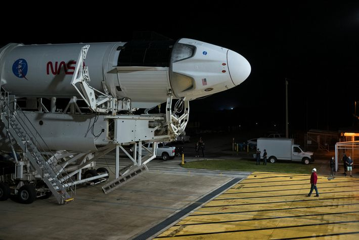 A SpaceX Falcon 9 rocket with the Crew Dragon spacecraft is seen as it is rolled ...
