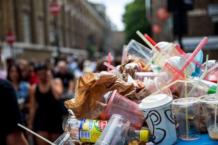 Rubbish overflows the bins on Brick Lane Market in London's East End. Plastic straws poke through ...