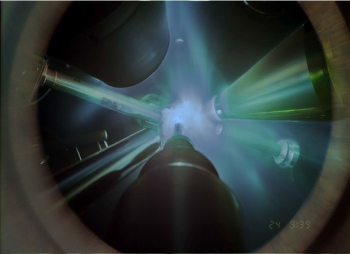 In this time-integrated photograph of an x-ray diffraction experiment, giant lasers focus on the water sample, ...