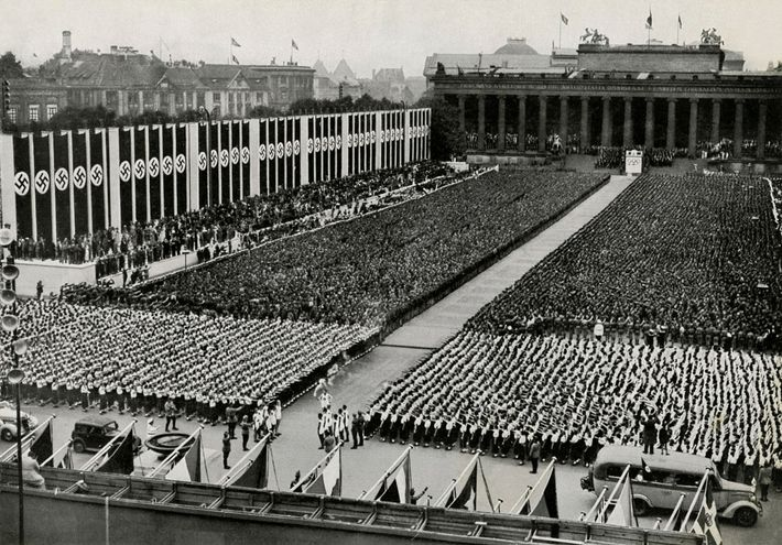 The Olympic flame arrives to a packed stadium covered with swastikas at the 1936 Berlin Olympics ...
