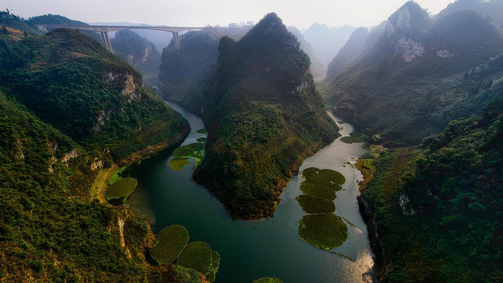 The gorges of Guizhou Province glimmer in the sunlight in China. Fossil teeth found in this ...