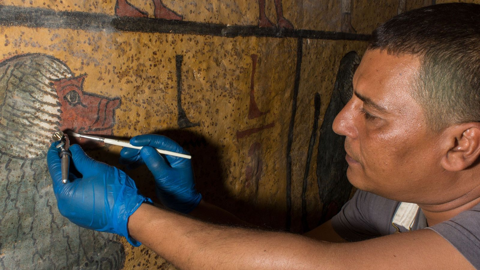 A conservator gently blows away sticky dust that has collected on the painted surfaces of Tutankhamun's ...