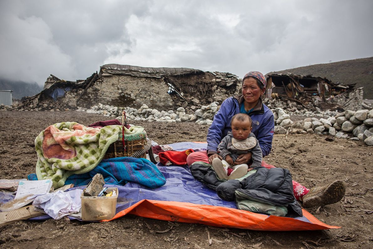 Mingma Phuti Sherpa and her son Lhakpa Tenzing take in the damage of their home in ...