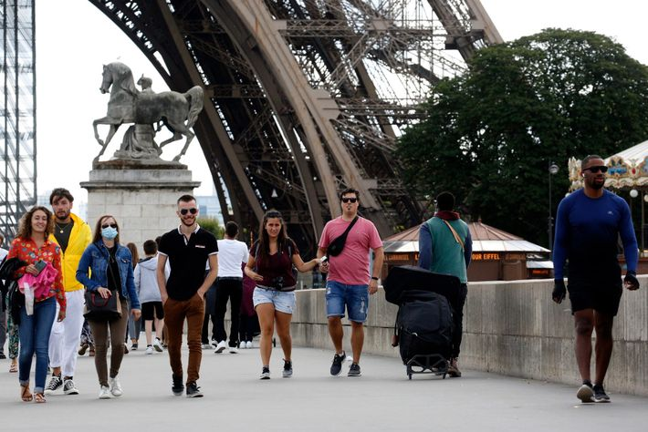 Strollers pass by the Eiffel Tower on July 26, 2020. France's strict lockdown this spring helped ...