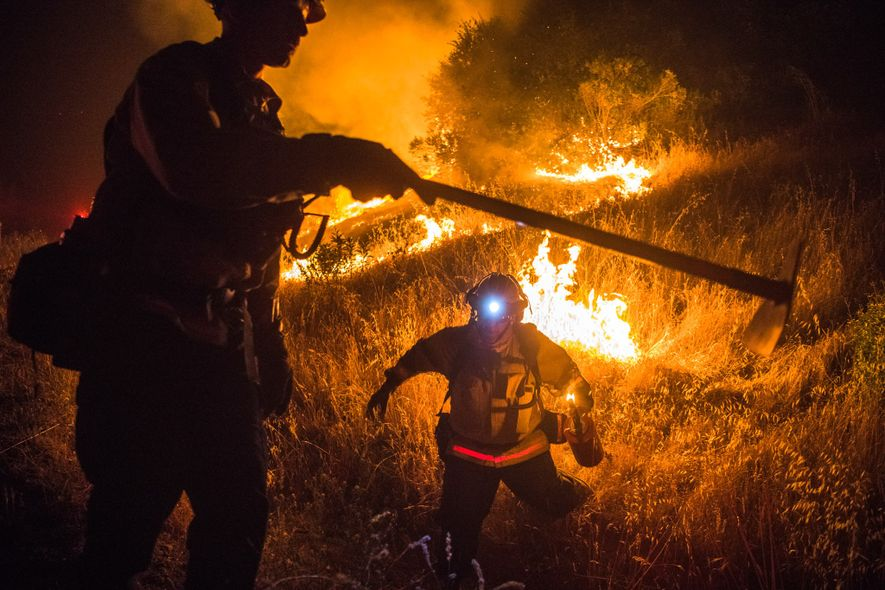 Monterey County fire captain John Hasslinger, left, and firefighter Patrick Tacheny, right, work to contain and …
