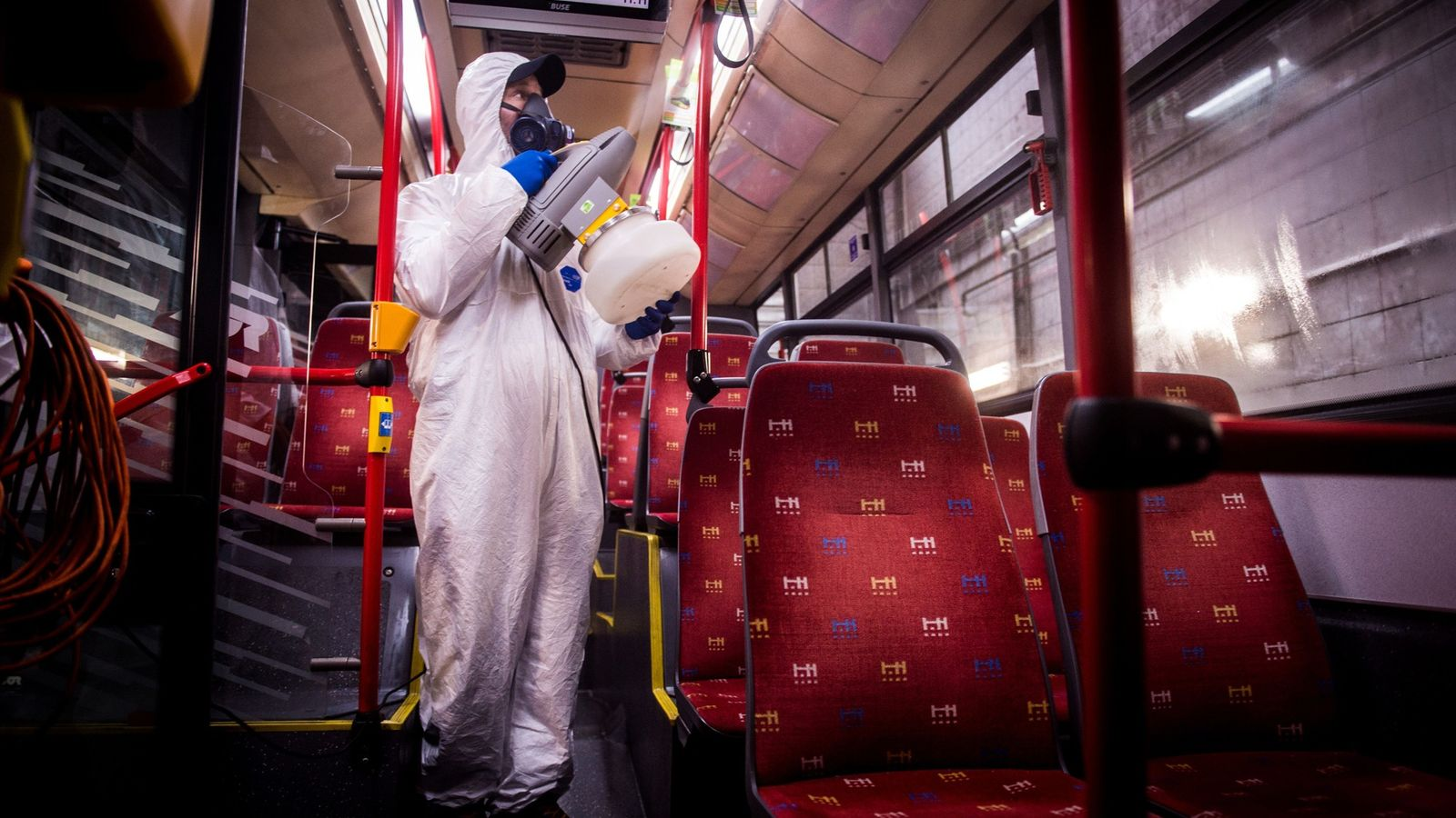 A worker wearing protective clothes disinfects the interior of a public bus in a bus-wash station ...