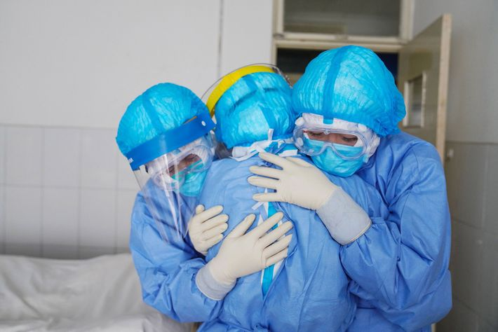 Medical staff members hugging each other in an isolation ward at a hospital in Zouping in ...
