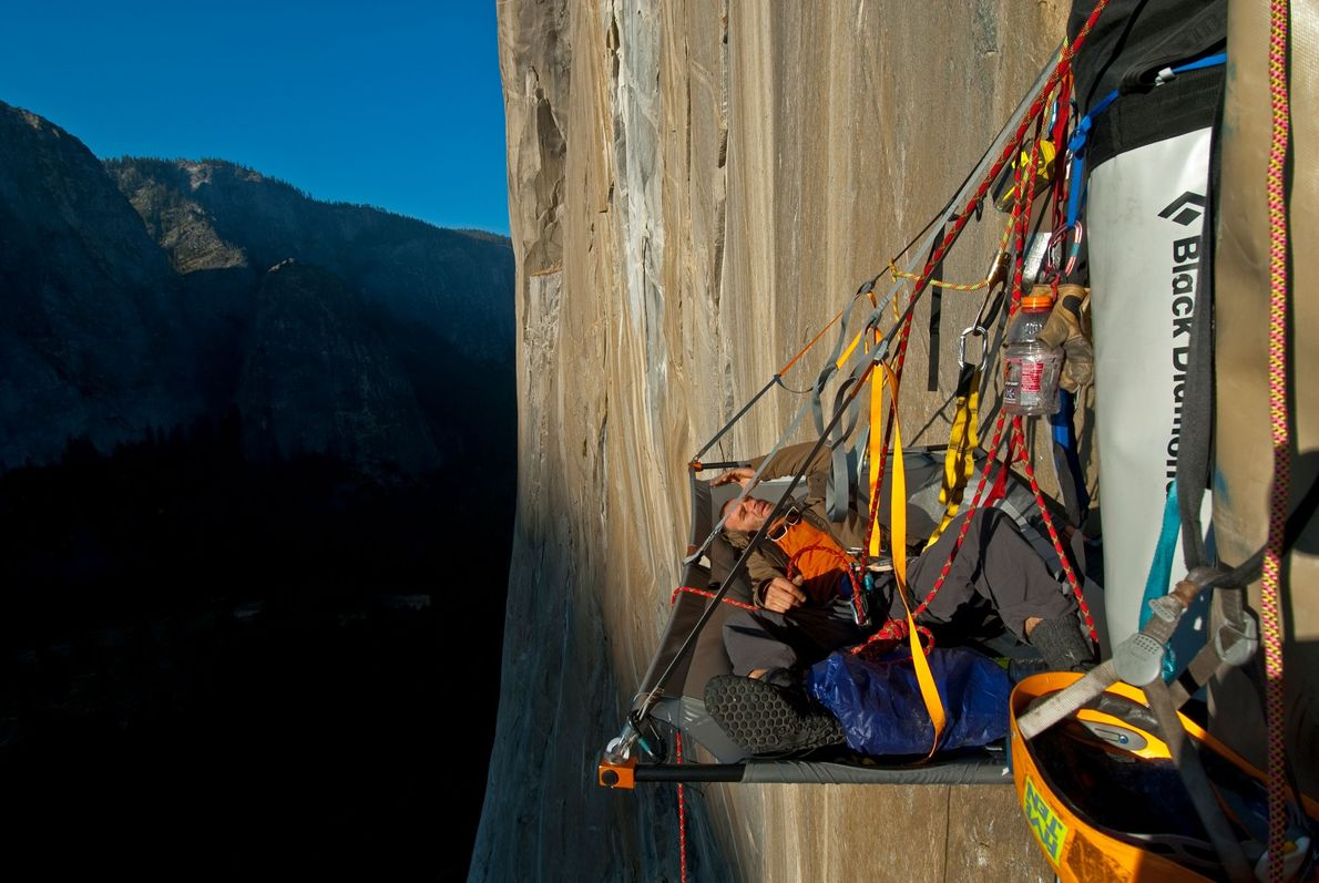 Climber Ivo Ninov rests while suspended against the face of El Capitan in Yosemite National Park.