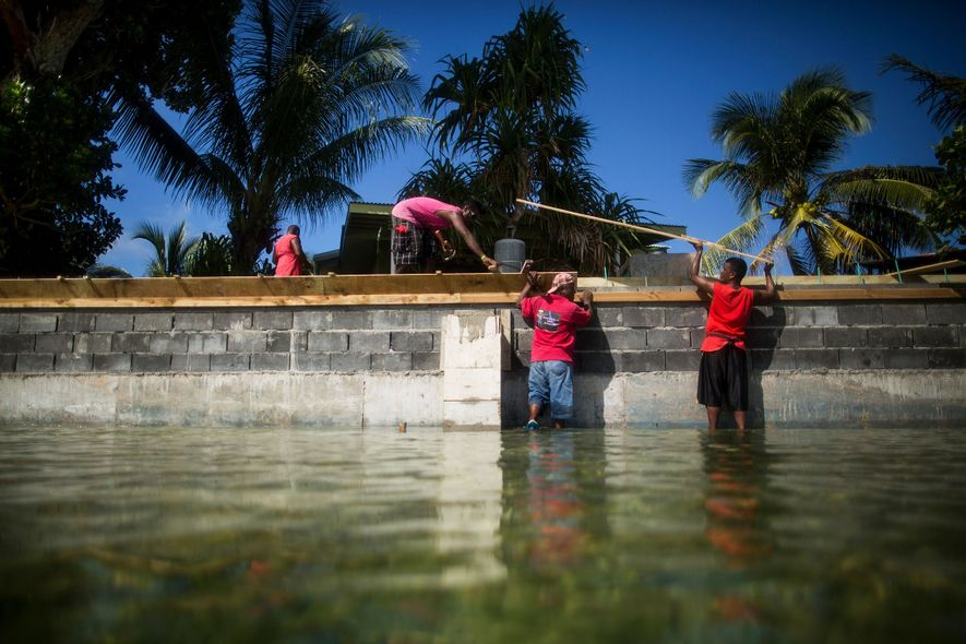 People rebuild a sea w​all on Ejit to try to hold back rising water.