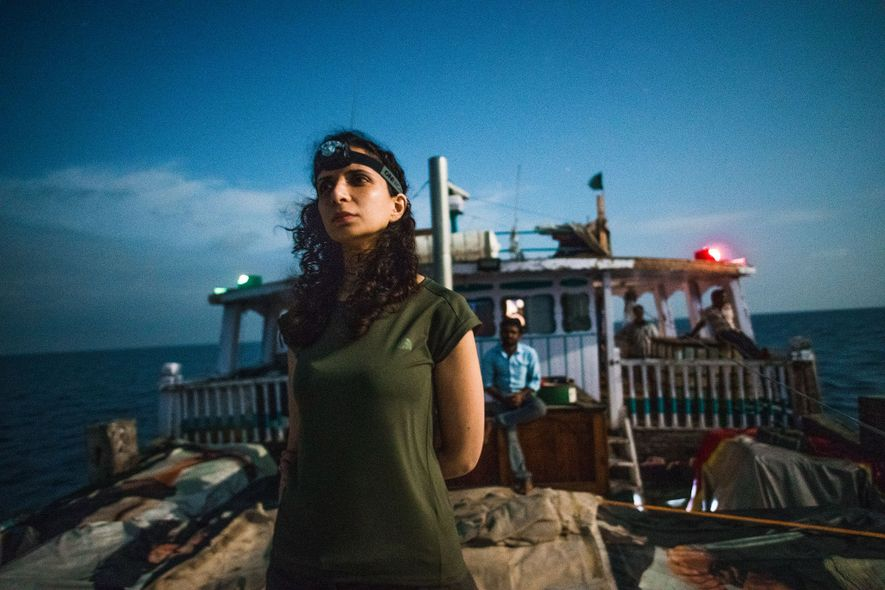 Ella Al-Shamahi, a paleonanthropologist and National Geographic Emerging Explorer, stands on the deck of the wooden ...