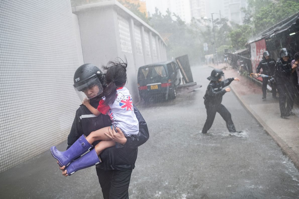 Police officers rush a young girl out of a collapsed school in Hong Kong. City officials ...