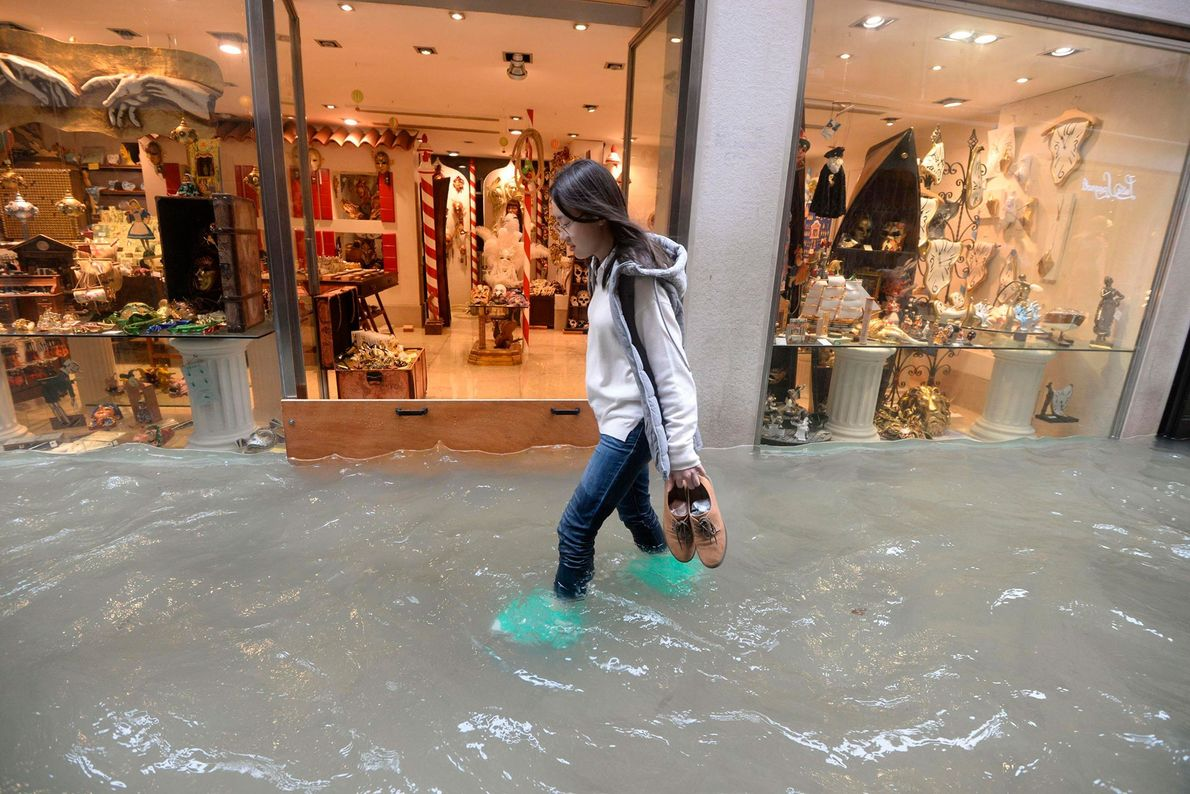 A woman walks in a flooded street in Venice. According to city officials, about 75 percent ...