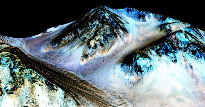 In Mars' Hale crater, 100-meter-long dark streaks (brown) are formed by flowing, liquid saltwater. They appear ...