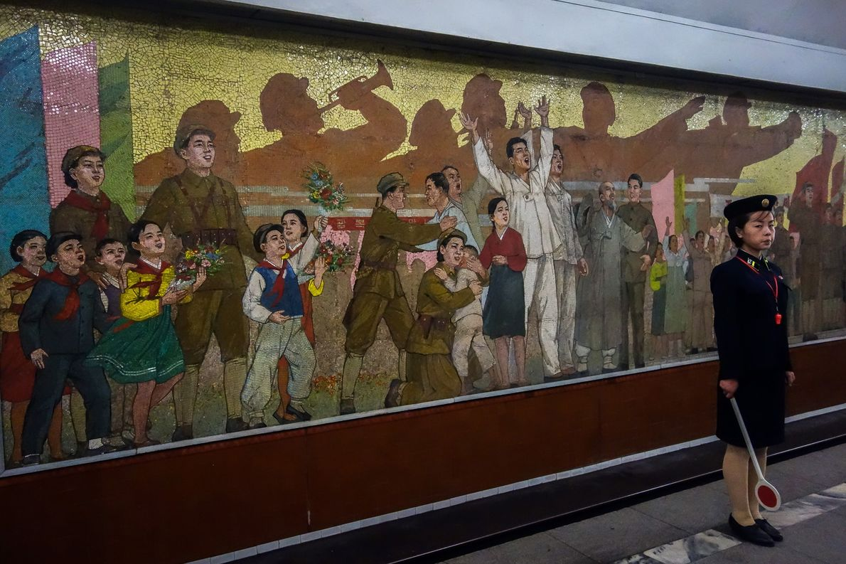 A train attendant stands in front of a mural that commemorates Korea's independence from Japan in …