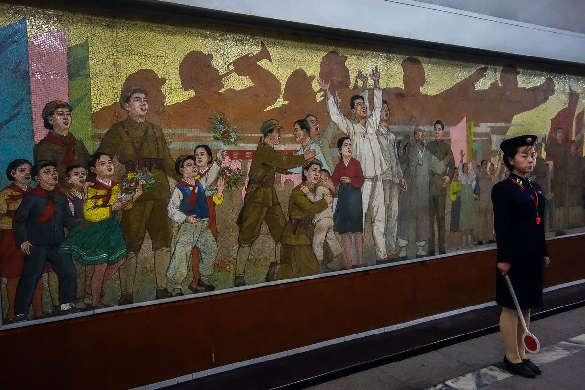 A train attendant stands in front of a mural that commemorates Korea's independence from Japan in ...