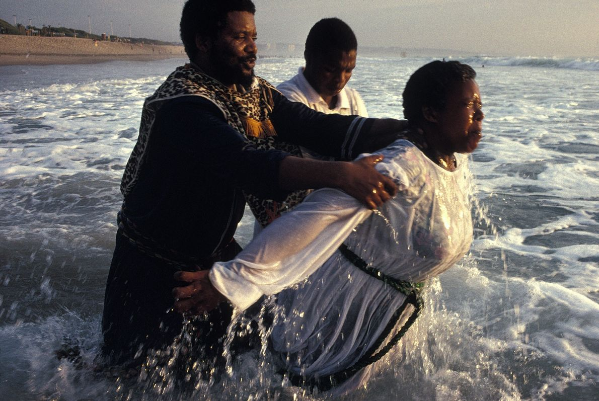 A member of the Church of Zion baptises a Zulu woman in the Indian Ocean near ...