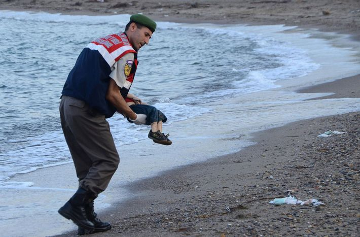 A Turkish police officer gently carries the body of three-year-old Aylan Kurdi after he washed ashore ...