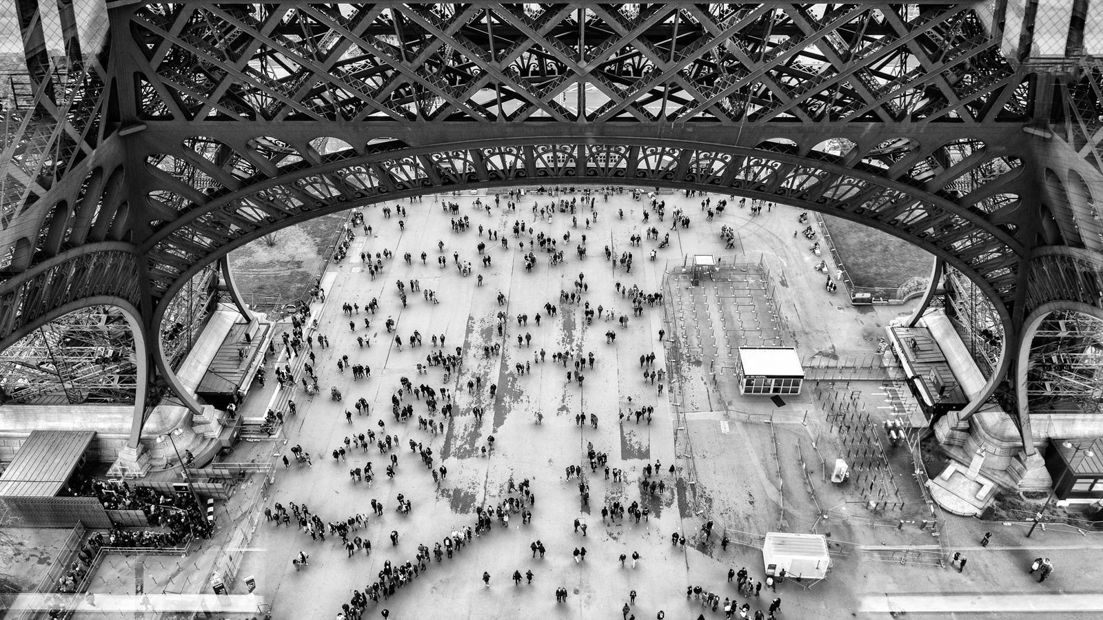 Crowds mass beneath the iconic structure of the Eiffel Tower.