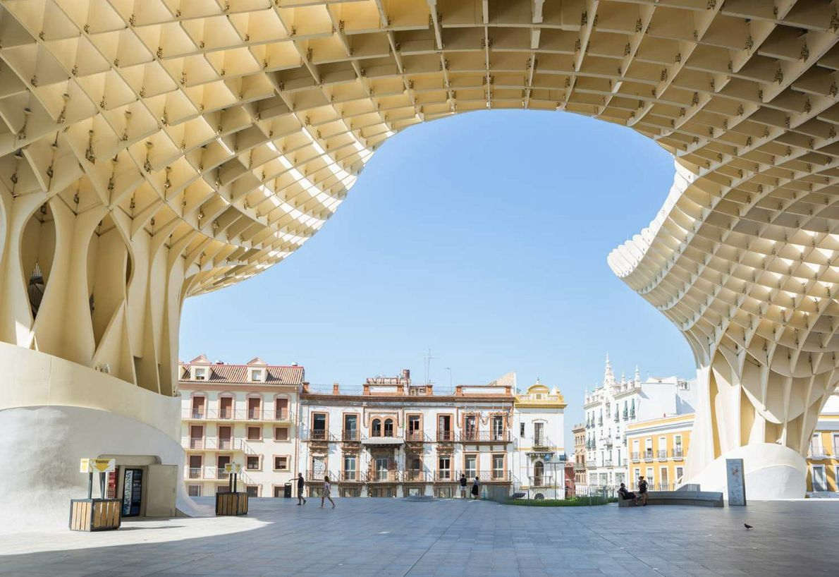 The modern lines of the Metropol Parasol frame the historic buildings of Seville, Spain, contrasting old ...