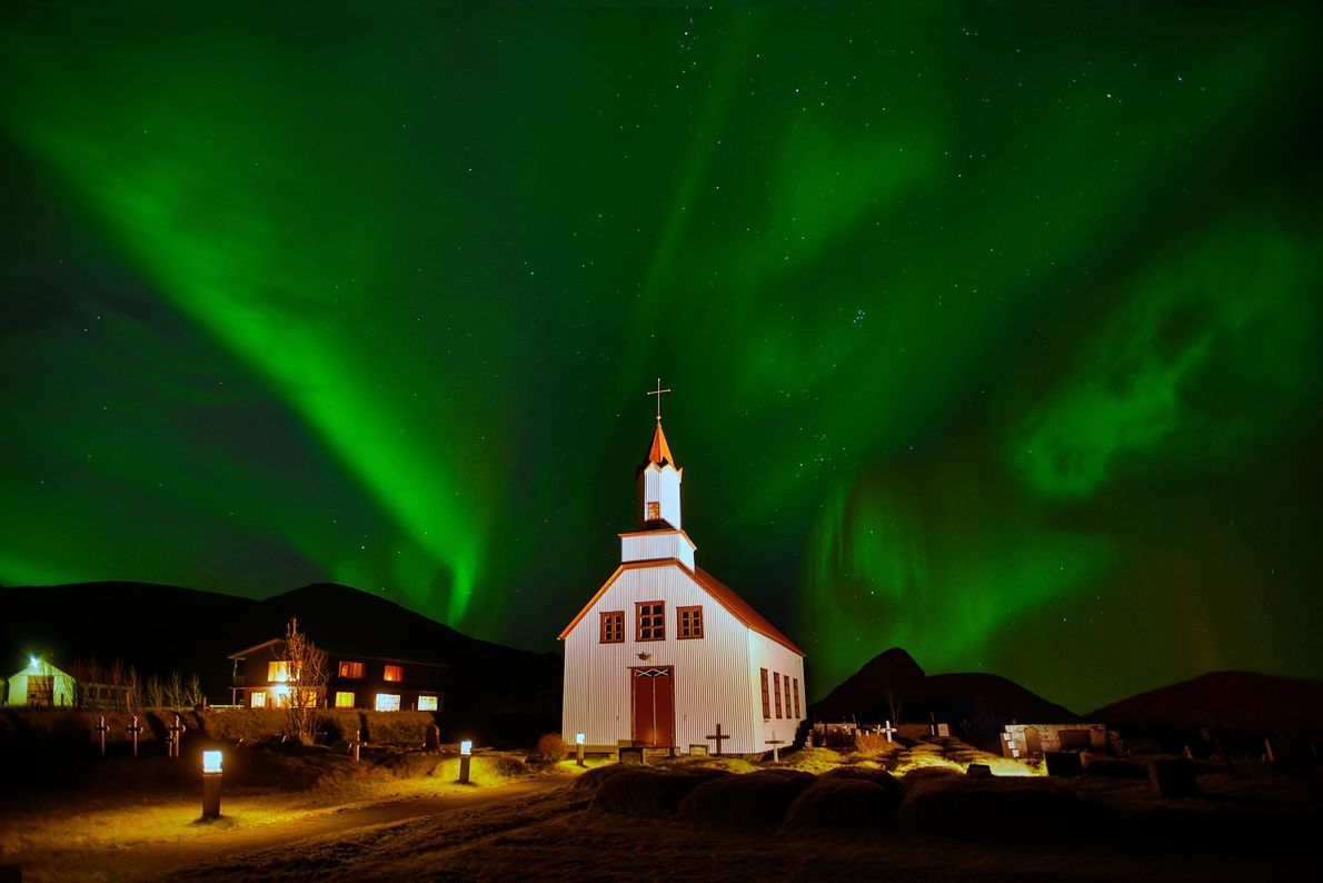 Northern lights turn the sky green behind a church in Iceland.