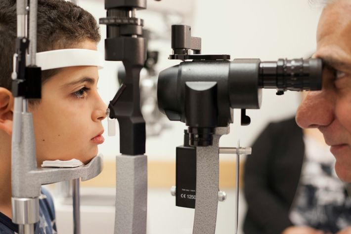 Albert Maguire checks the eyes of Misa Kaabali, 8, at the Children's Hospital of Philadelphia in ...