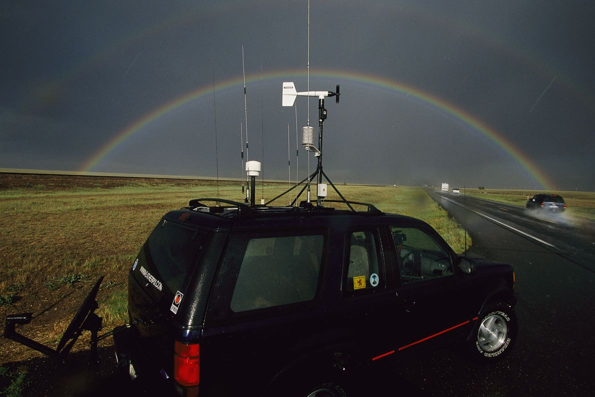 Tornado chasers study a dark sky with a perfectly arced rainbow. Storm chasers drive a fine ...