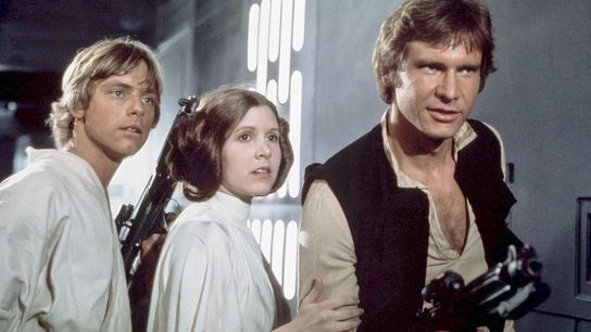 Carrie Fisher in the role that made her famous forever, Princess Leia, alongside Harrison Ford (right).