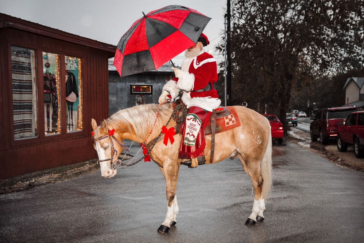 In 2016, Cowboy Kringle poses for photos in historic Gruene, Texas before ceremoniously riding through town ...