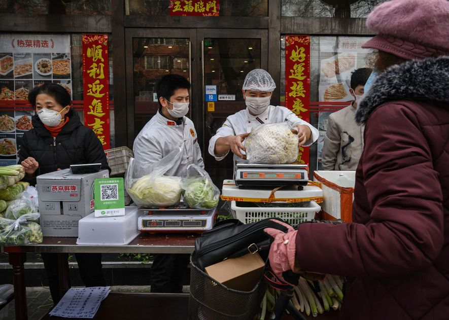 Vendors in Beijing wear protective masks as they sell vegetables. A 2014 study found that only ...