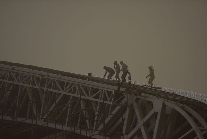 Laborers at Noida stadium amid a sudden heavy dust storm, on May 2, 2018 in Noida, ...