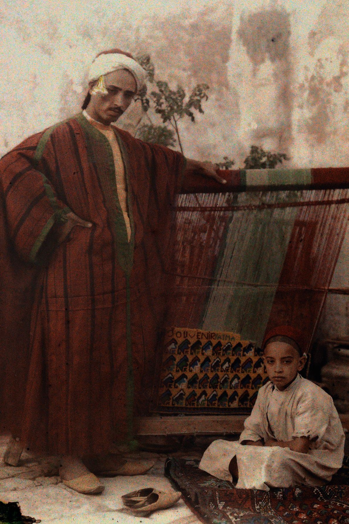A father and son in the early 1900s pose next to a weaving machine in Tunisia.