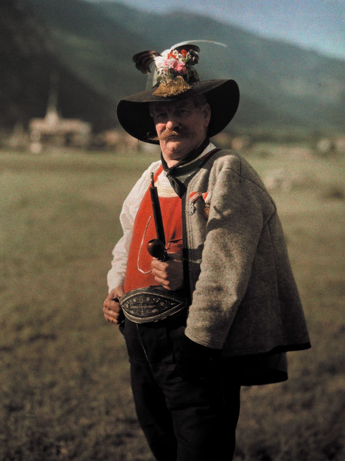 A man from Zillertal, Austria, wears an elaborate hat decorated with feathers, flowers, and gold-colored tassels.