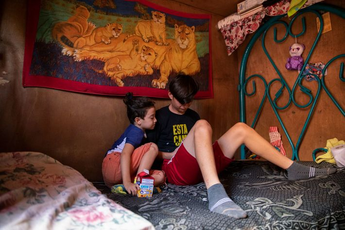 Telma's grandson, Gabriel, and her son, David, play video games in her cabin. After three decades ...