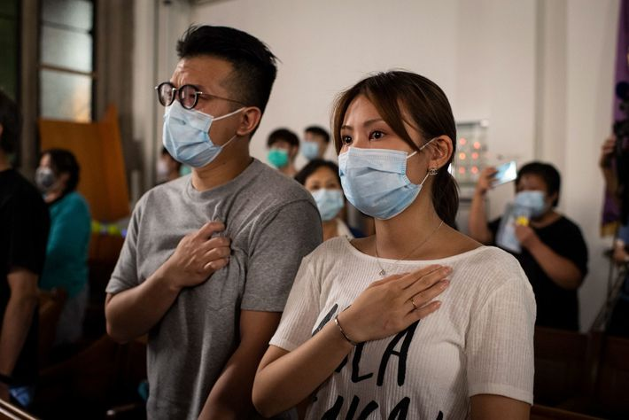 "A woman and a man tear up while singing ""Glory to Hong Kong,"" the protest movement's ..."