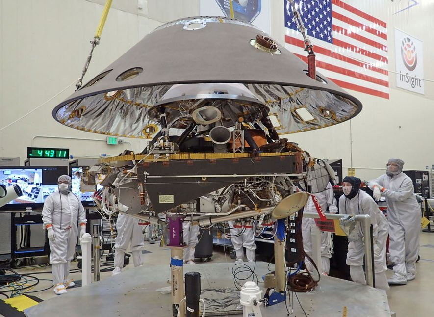 The back shell of NASA's InSight spacecraft gets lowered onto the mission's lander, which is folded ...