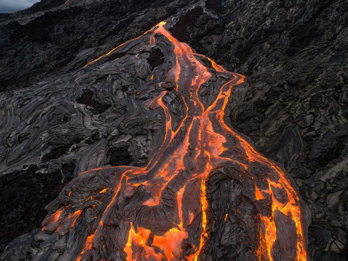 A drone captures lava as it slides down the side of the mountain.