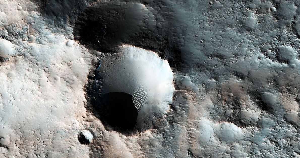 This enhanced colour image shows several craters somewhere in the southern mid-latitudes of Mars. The bluish ...