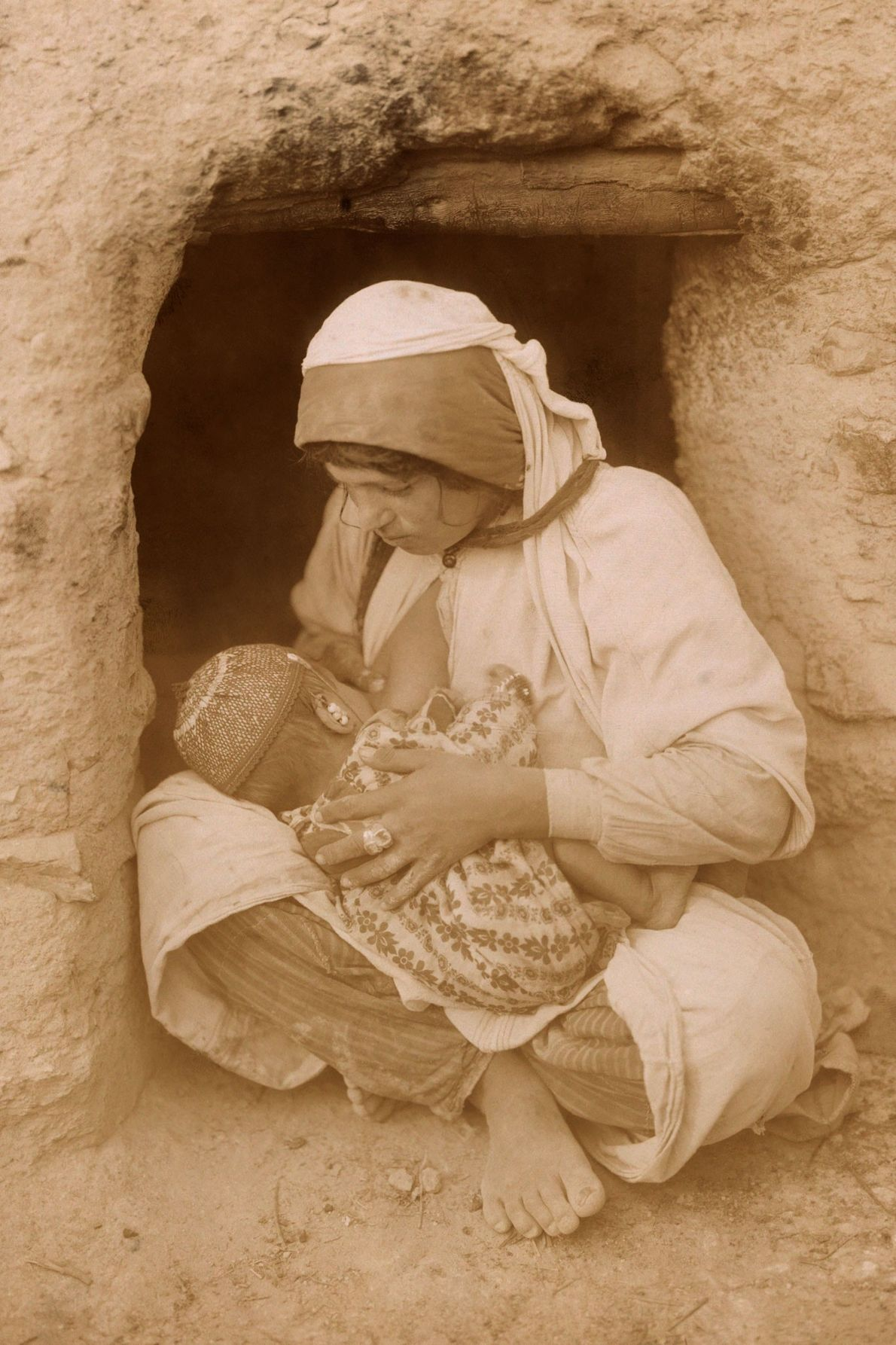 A mother in the Middle East breastfeeds her baby as she sits outside her home.