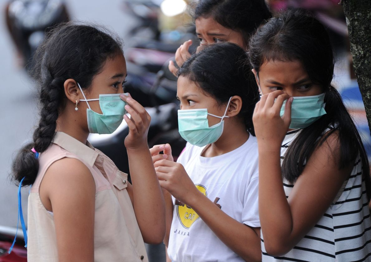 Young people put on masks to protect themselves from ash in the air.