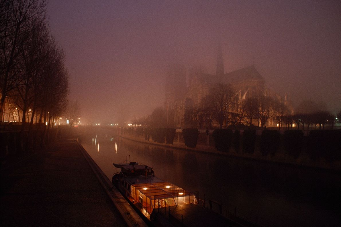 A night view from the 1980s shows the shadowy cathedral from across the Seine.