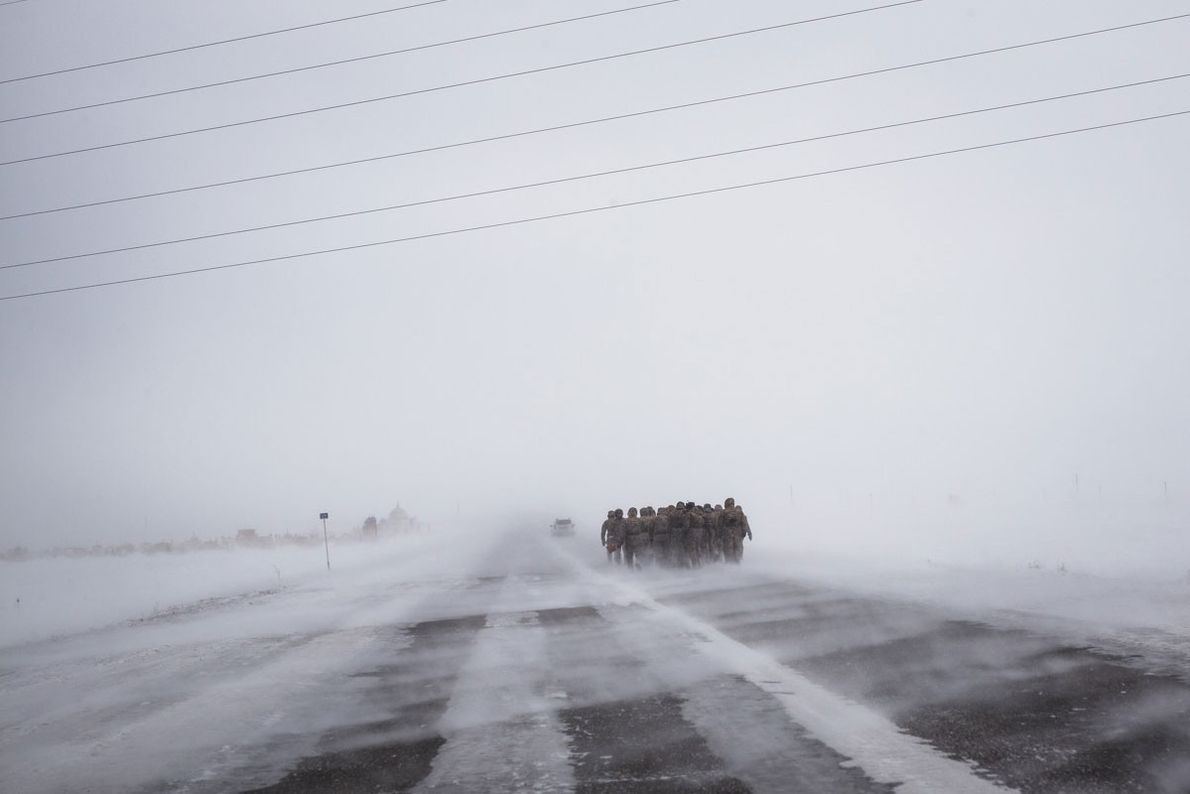 Soldiers walk on a windswept road on the edge of Semey.