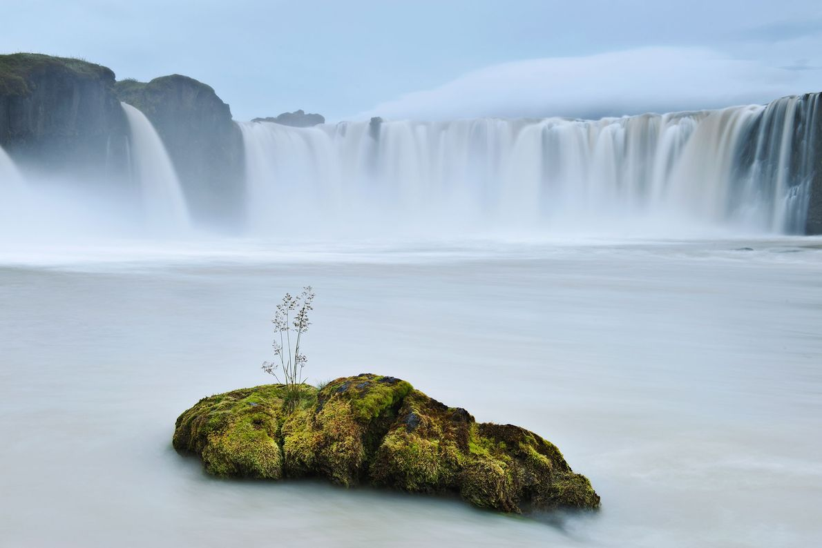 A glacial waterfall cascades over a 40-foot-high ledge at Godafoss, Iceland.